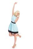 Tanzendes blondes Mädchen im blauen Pastellkleid Stockfoto