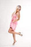 Tanzendes blondes Mädchen im kurzen Rosa   Kleid und hohe Absätze auf ihren sexy Beinen lokalisiert auf Weiß, Rückseite lizenzfreies stockfoto