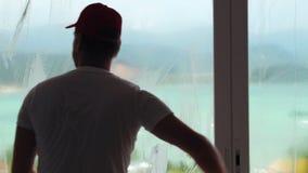 Tanzendes und waschendes Glas des glücklichen Fensterputzers während der Haushaltung stock footage