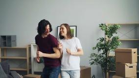 Tanzendes zu Hause lächeln des jungen Mannes und der Frau, den Spaß habend, der Verlegung feiert stock footage