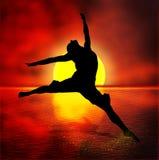 Tanzenfrau, die über den Ozean bei Sonnenuntergang springt Lizenzfreie Stockbilder
