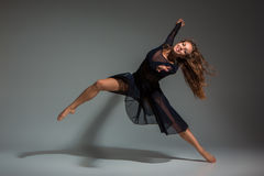 Tanzenfrau in einem schwarzen Kleid Zeitgenössischer moderner Tanz auf einem grauen Hintergrund Lizenzfreies Stockbild