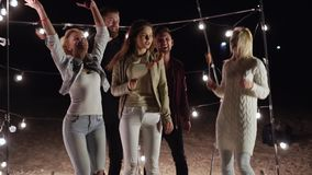 Tanzenfreunde mit Aufsteckspindeln in ihren Händen, die Spaß auf dem Abendstrand im Hintergrund eines Dekors mit Lampen haben stock video footage