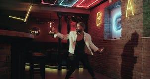 Tanzenmann in der Stange mit erstaunlichen Lichtern, hält er den Smartphone und macht Fotos stock video footage