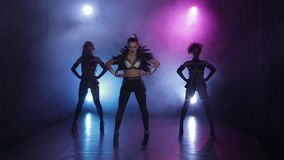 Tanzgruppe von drei Mädchen fangen ihre Darstellung an Rauchiger Hintergrund