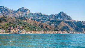 Taormina city and Giardini Naxos town on coast. Travel to Italy - Taormina city on mountain and Giardini Naxos town on waterfront of Ionian sea in Sicily in royalty free stock image