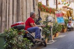 Taormina Italien, 08/30/2016: En man sitter p? en sparkcykel i skuggan arkivfoton