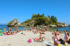 TAORMINA, ITALY - JUNE 20, 2019: bathers on the beach of Taormina with Isola Bella island on the background.  stock images