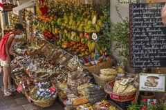 Taormina, Italy, 08/30/2016: A narrow street in the old town. People buy fruits and souvenirs. Horizontal stock image