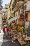 Taormina, Italy, 08/30/2016: A narrow street in the old town. People buy fruits and souvenirs. Vertical stock photo