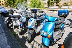 Taormina, Italy, 08/30/2016: Parking scooters on a city street royalty free stock image