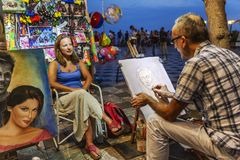 Taormina, Italy, 08.29.2016: A street artist paints a portrait of a girl in the evening on the town square stock photos