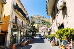 Taormina, Italy, 08/30/2016: A street in the old town with walking tourists on a bright sunny day. Horizontal royalty free stock image
