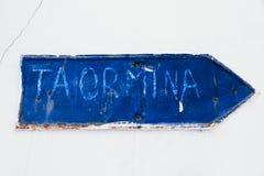 Taormina manuell geschrieben in einen blauen rostigen und Schmutzmetalleisen-Plattenpfeil mit Schalenbeschichtung und -kratzern Lizenzfreies Stockbild