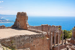 Taormina's theater and Naxos. Greek theater in Taormina with the Giardini Naxos bay in the back in Sicily, Italy Royalty Free Stock Images