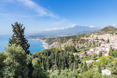 Taormina at Sicilian coast with smoking Etna in the distance Royalty Free Stock Photography
