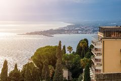 Taormina, Sicily - Beautiful view of the famous hilltop town of Taormina with palm tree. Mediterranean sea and sunshine Stock Images