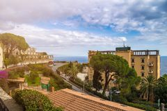 Taormina, Sicily - Beautiful view of the famous hilltop town of Taormina with palm tree, mediterranean sea Stock Images