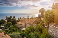 Taormina, Sicily - Beautiful view of the famous hilltop town of Taormina with palm tree, mediterranean sea Stock Image