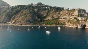 Taormina, SICILY, Italy - August 2019: Sailing yachts and boats near the rocky shore of the ocean. Aerial drone shot.  stock video