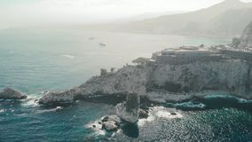 Taormina, SICILY, Italy - August 2019: unrecognized hotel resort on a rocky mountain by the ocean. Foamy water waves. Rocks. The concept of an expensive luxury stock footage