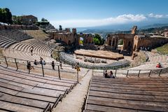 TAORMINA, SICILY / ITALY - SEPTEMBER 30, 2018: Ruins of the Ancient Greek Theater in Taormina city and people enjoying perfect sun. Ny weather stock images
