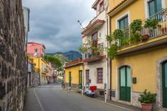 Taormina, Sicily - Typical italian romantic street of Taormina, the lovely hilltop town. On the island of Sicily with parking scooter and hills at background royalty free stock image