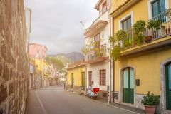 Taormina, Sicily - Typical italian romantic street of Taormina. The lovely hilltop town on the island of Sicily with parking scooter and hills at background royalty free stock photography