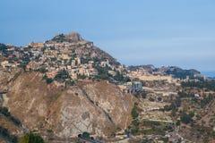 Taormina står kick på klippan som förbiser det medelhavs- havet royaltyfri foto