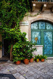 Taormina street with greenery. Quite street in Taormina, Sicily, Italy with decorated glass door and greenery royalty free stock photos
