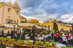 Taormina town - main square, Sicily. People in restaurants on main square in Taormina town. Famous city to visit in Italy. 30 December 2018 royalty free stock photography