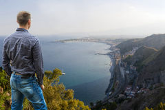 Taormina View. Man Standing High Looking Far into Distance along Mediterranean Coastline in Sicily Stock Image