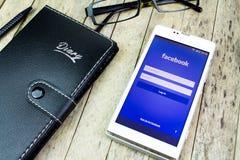 TAPÓN KAN, TAILANDIA - 9 DE OCTUBRE DE 2015: cuaderno, vidrios, pluma, teléfono elegante con Facebook app imagen de archivo