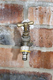 Tap. Outside tap on brick wall, in garden Stock Photos