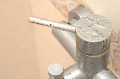 Tap in bathroom. It is a modern stainless steel tap in bathroom, with water droplet Stock Photography