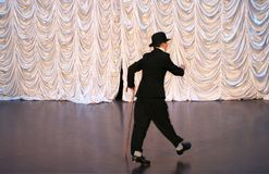 Tap dance with a cane in a black hat. Dance step. A man is dancing on stage royalty free stock photo