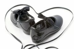 Tap dance shoes and heart. Patent leather tap dance shoes enclosed in a black, artfully arranged, heart made of ribbon Royalty Free Stock Photo