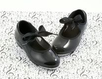 Tap dance shoes and music. Black tap dancing shoes on music symbols Royalty Free Stock Photography