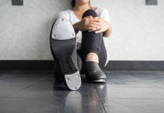 Tap dancer sitting down in tap class holding one of her legs. With a close up of her tap shoe in dance class royalty free stock photo