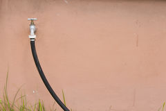 Tap and garden hose. Abstract background with tap and black garden hose stock images