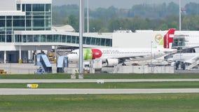 TAP het vliegtuig van Luchtportugal op baan in de Luchthaven van München, Duitsland, de Wintertijd met sneeuw stock video