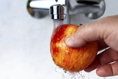 From the tap pours water on Apple. From the tap water pours on the apple royalty free stock image