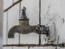 A tap protruding from a wall. Made of white blocks royalty free stock photography
