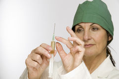 Tap at the syring. Head-and-shoulder view of a middle-aged woman with green scrub Cap against a white background, holding a filled syringe before him Stock Photo