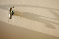 Tap on the wall. Shadow of tap on the wall stock image