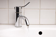 Tap Water. Close up of sink and tap with running water in bathroom Royalty Free Stock Photo