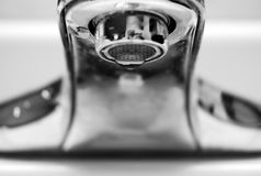 Tap Water Sink Faucet. A silver and shiny tap water sink faucet with a barely noticeable drop of water dripping out of the faucet. Lots of copyspace below with Royalty Free Stock Photo
