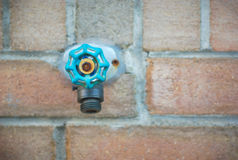 Tap water spigot on brick wall, aqua blue green valve Stock Photo