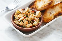 Tapa cuttlefish. Mediterranean food, delicious spicy cuttlefish with garlic with toast bread Royalty Free Stock Photo