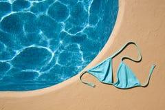 Tapa de bikiní azul en el poolside Foto de archivo libre de regalías